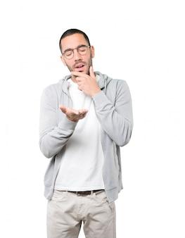 Twijfelachtige jonge man die iets met zijn hand houdt