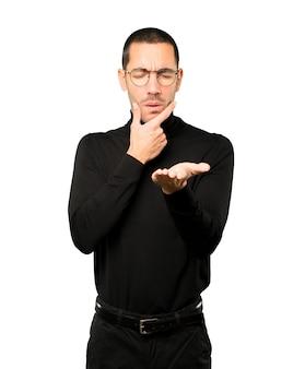Twijfelachtige jonge man die iets met zijn hand vasthoudt