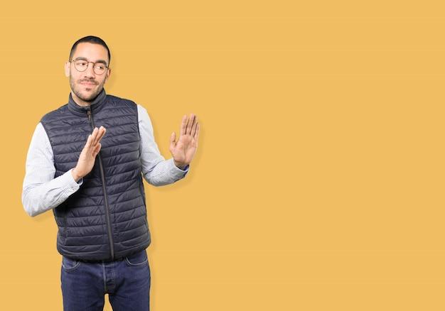Twijfelachtige jonge man doet een gebaar van blijf kalm