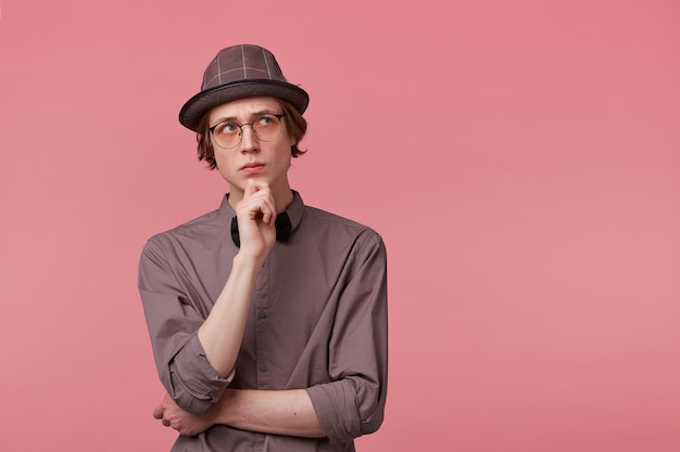 Twijfelachtige jonge, netjes geklede man staat met zijn hand op een kin en kijkt bedachtzaam rechtsboven, bezorgd, nadenkend over een probleem, bang voor iets, over roze achtergrond