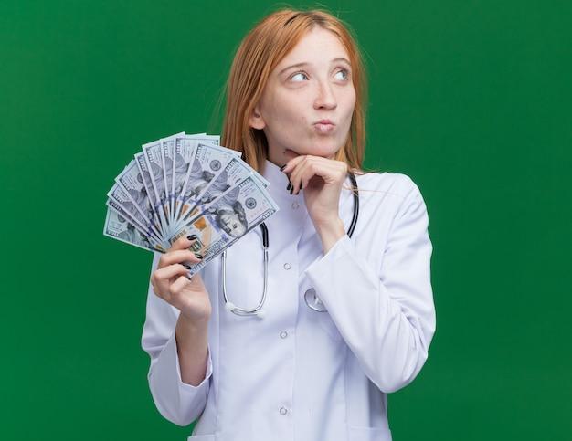 Twijfelachtige jonge vrouwelijke gemberdokter met een medisch gewaad en een stethoscoop die geld vasthoudt en de kin aanraakt en naar de zijkant kijkt