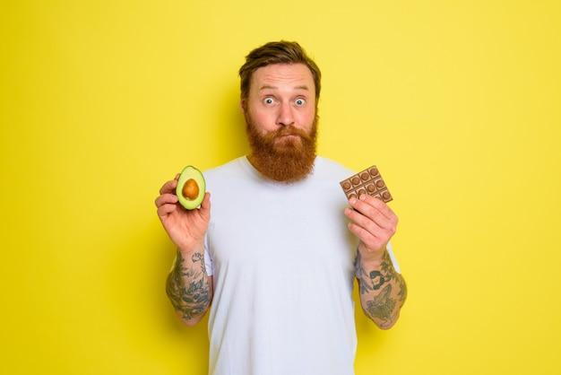 Twijfelachtige man met baard en tatoeages houdt avocado en chocolade vast