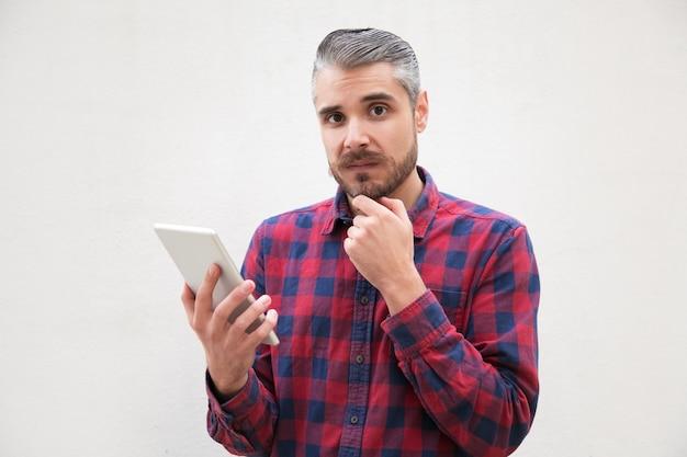 Twijfelachtige mens die digitale tablet houdt