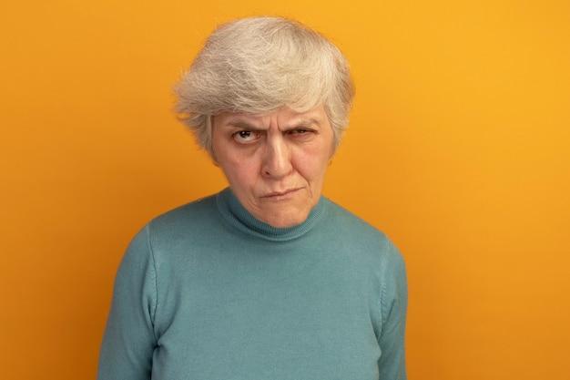 Twijfelachtige oude vrouw die een blauwe coltrui draagt en naar de voorkant kijkt geïsoleerd op een oranje muur met kopieerruimte