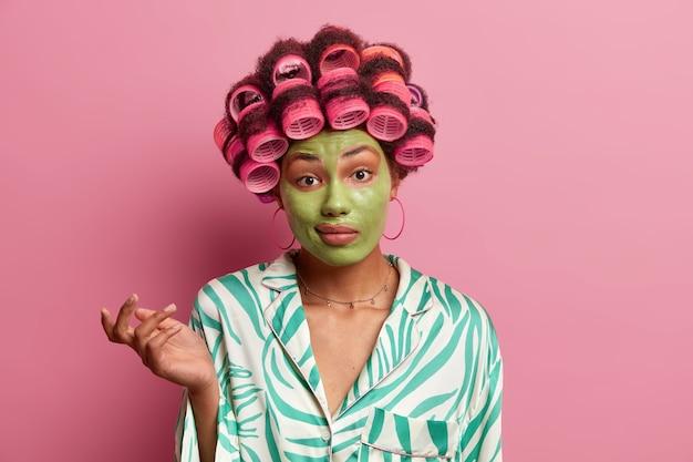 Twijfelachtige perplexe huisvrouw denkt na over de juiste beslissing, haalt verbijsterd haar schouders op, gekleed in pyjama, maakt kapsel met rollers, past een groen schoonheidsmasker toe voor een verfrissende huid en teint