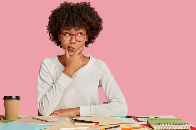 Twijfelachtige student studeert kunst, besteedt tijd aan het maken van schetsen, houdt kin vast en tuitt lippen met aarzeling, denkt na over wat te doen, kijkt met een besluiteloze uitdrukking opzij op kopie ruimte, geïsoleerd op roze