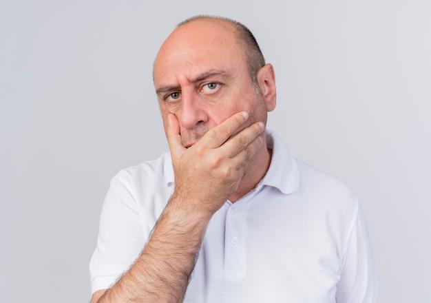 Twijfelachtige toevallige volwassen zakenman die camera bekijkt die hand op mond houdt die op witte achtergrond wordt geïsoleerd