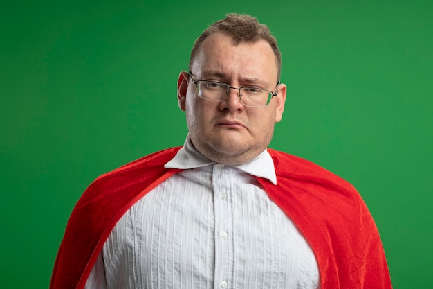 Twijfelachtige volwassen slavische superheld man in rode cape bril geïsoleerd op groene muur