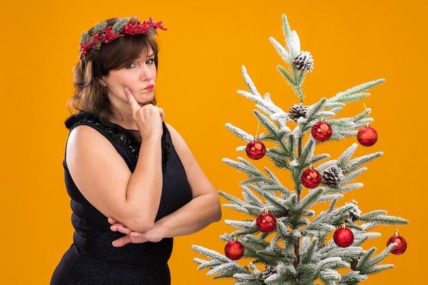 Twijfelachtige vrouw van middelbare leeftijd die de hoofdkrans van kerstmis en klatergoudslinger om hals draagt die zich dichtbij verfraaide kerstboom in profielmening bevindt die gezicht aanraakt