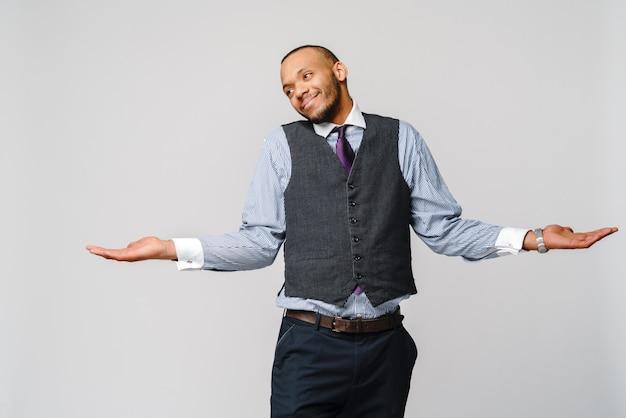 Twijfelconcept - jonge afrikaanse amerikaanse zakenman die band en over lichtgrijze muur clueless en verwarde uitdrukking met opgeheven armen en handen dragen.