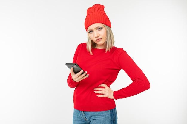 Twijfelend blondemeisje met een smartphone in haar handen die op een wit met exemplaarruimte redeneren
