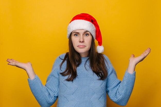 Twijfelend jong meisje haalt schouders op, kijkt onzeker, verward en kijkt naar handpalmen, draagt kerstmuts en blauwe trui, geïsoleerd op gele studiomuur. nieuwjaarsviering prettige vakantie