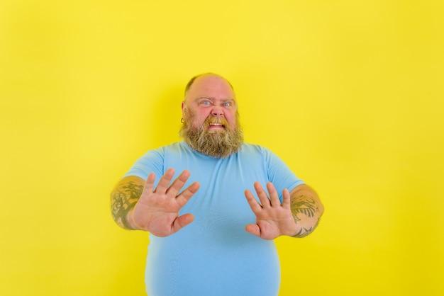 Twijfelman met baard en tatoeages twijfelt en is ergens bang voor