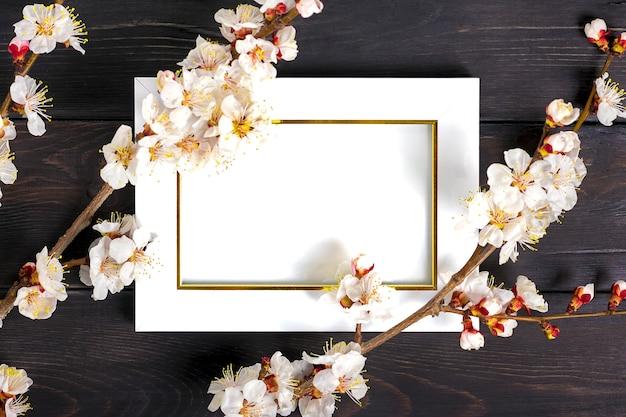 Twijgen van de abrikozenboom met bloemen en wit fotokader op houten achtergrond.