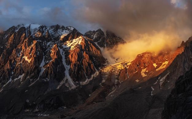 Twilight bergen. majestueuze gletsjer wordt verlicht door de heldere gouden avondzon. panoramisch zicht. grote aktru-gletsjer, altai-gebergte.
