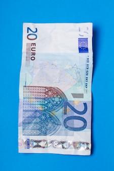 Twintig euro-factuur gerimpeld over een blauwe achtergrond.