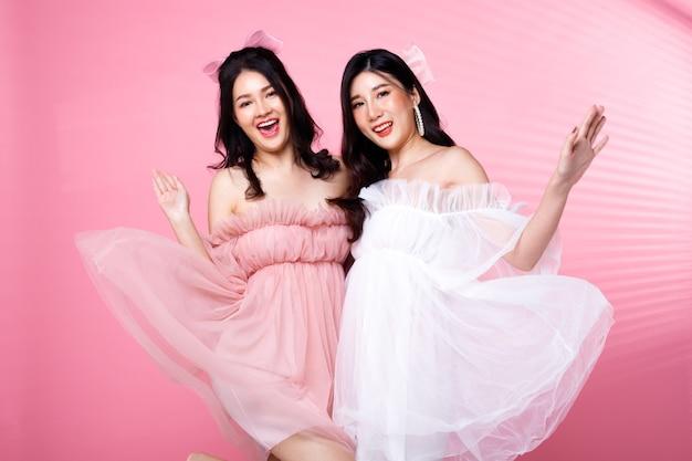 Two fashion beauty women heeft zwart haar springen en uiten een gevoel van glimlach. aziatische meisjes dragen roze jurk over roze toonmuur met raamstreep schaduw middagmuur, kopie ruimte