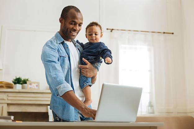 Typen. aantrekkelijke waakzame jonge afro-amerikaanse vader die zijn zoontje vasthoudt en op de laptop typt terwijl hij aan de tafel en een open haard op de achtergrond staat