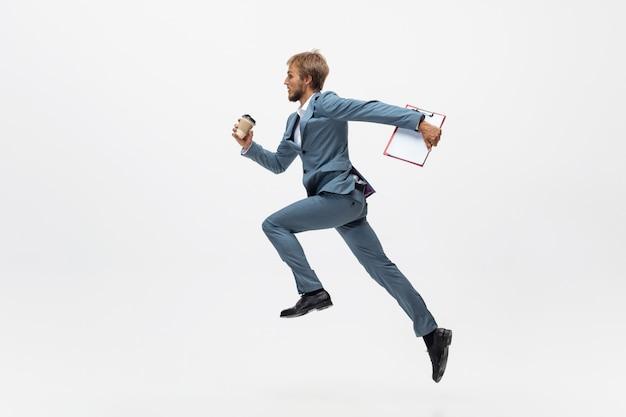 Typen. man in kantoor kleding lopen, joggen op witte ruimte zoals professionele atleet, sportman. ongewone look voor zakenman in beweging, actie met bal. sport, gezonde levensstijl, creativiteit.