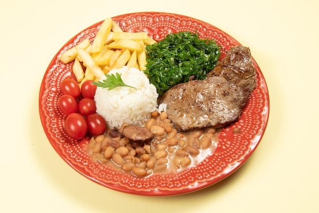 Typisch braziliaans basisgerecht met rijst, bonen, biefstuk, frites, gesmoorde kool en tomaat in een rood gerecht op bovenaanzicht