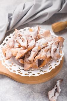 Typisch italiaanse carnaval beignets bestrooid met poedersuiker op betonnen tafel.