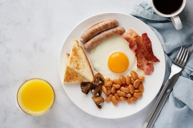 Typisch klassiek engels ontbijt heerlijke eieren spek champignons bonen en worstjes op plaat