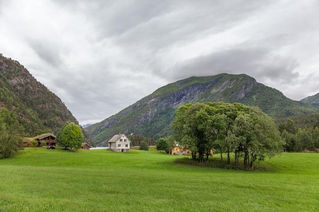Typisch landschap noors landschap met huis. bewolkte zomerochtend in noorwegen, europa.