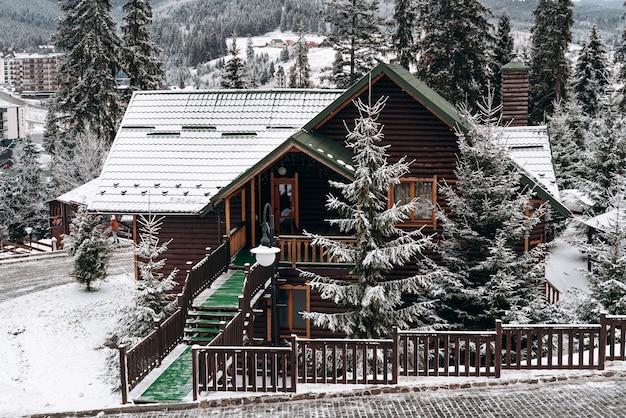 Typisch landschap van de bergen met privélandgoederen in de winter. volledige lengte weergave van het winterhuis met bossen in de sneeuw. stock foto