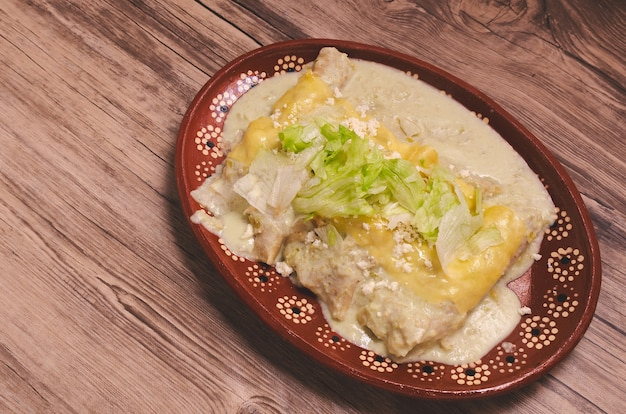 Typisch mexicaans eten groene enchiladas op houten tafel