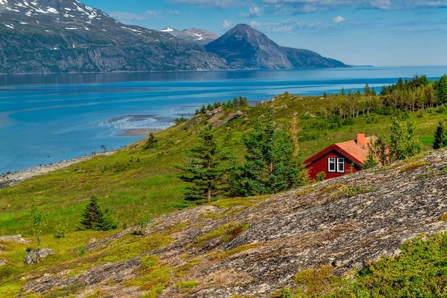 Typisch noors rood huis op de achtergrond van een pittoresk fjord