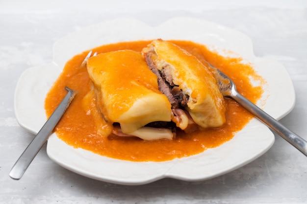 Typisch portugees eten francesinha in witte schotel met vork en mes