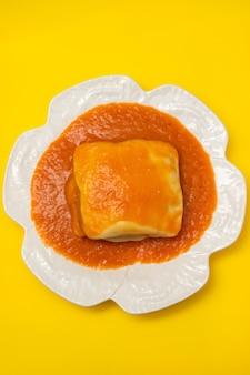 Typisch portugees eten francesinha in witte schotel