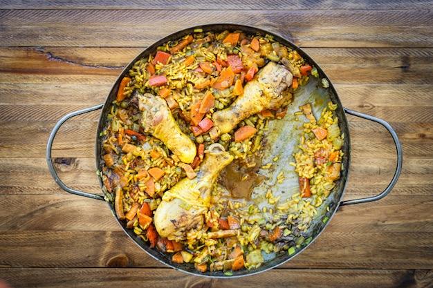 Typisch spaans eten van arroz con pollo of kippenpaella in een paellapan die een portie mist. etnisch of regionaal voedselconcept.