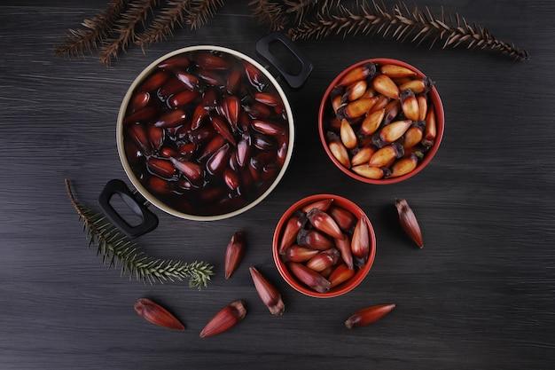 Typische araucaria-zaden die in de winter als kruiderij in de braziliaanse keuken worden gebruikt. bovenaanzicht braziliaans rondsel in de pot op een grijze ondergrond.