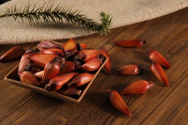 Typische araucaria-zaden die in de winter als kruiderij in de braziliaanse keuken worden gebruikt. bovenaanzicht braziliaans rondsel op houten tafel.