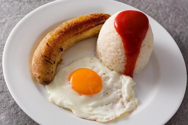 Typische cubaanse rijst met gebakken banaan en gebakken ei op een plaat op grijze oppervlak