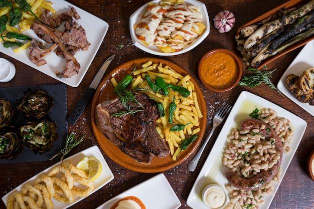 Typische gemengde spaanse gerechten op donkerbruine houten tafel. bovenaanzicht