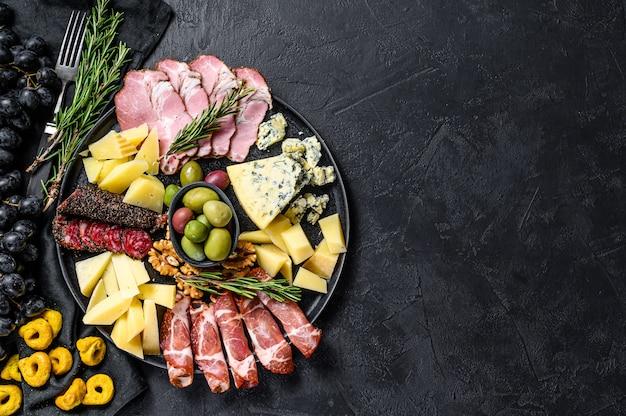 Typische italiaanse antipasto met prosciutto, ham, kaas en olijvenachtergrond
