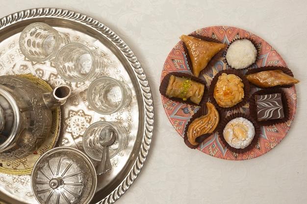 Typische marokkaanse desserts vergezeld van thee van bovenaf gezien.