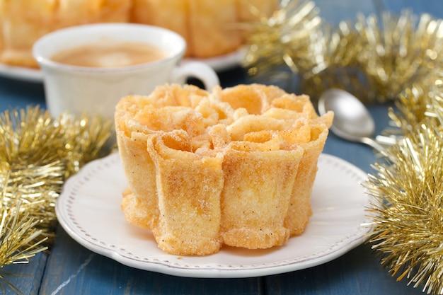 Typische portugese dessertfilhos op witte plaat op blauwe houten oppervlakte en kop van koffie
