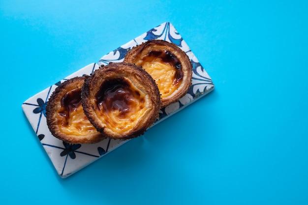 Typische portugese ei taart pastel de nata op blauw papier achtergrond