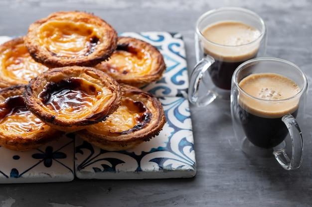 Typische portugese eitaart pastel de nata met kopje koffie op keramische achtergrond