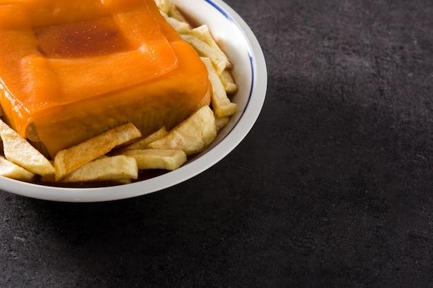 Typische portugese francesinha sandwich met frietjes op zwarte ondergrond exemplaarruimte