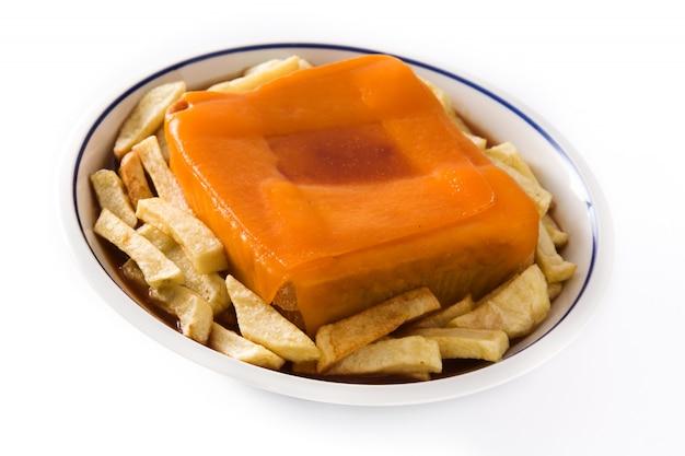 Typische portugese francesinhasandwich met frieten die op witte oppervlakte worden geïsoleerd