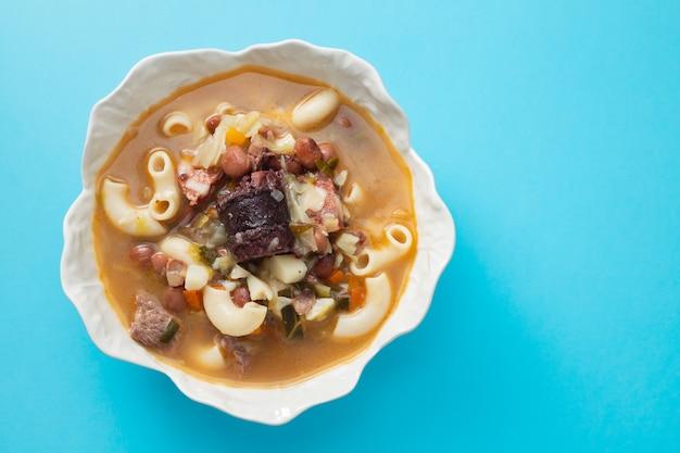 Typische portugese soep sopa a lavrador in mooie schotel op blauwe achtergrond