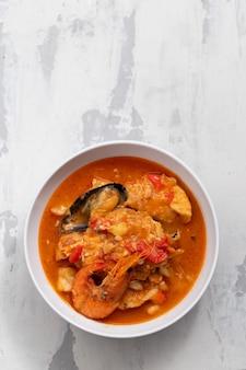 Typische portugese stoofpot van vis en zeevruchten caldeirada in schotel op keramisch oppervlak