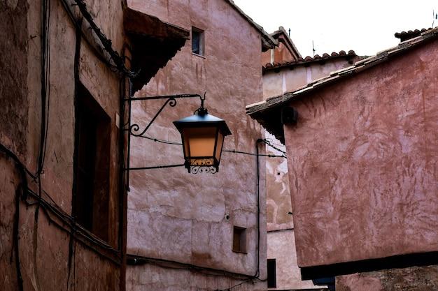 Typische smalle roodachtige straat van een middeleeuws dorp met een oude lantaarnpaal