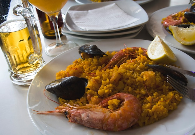 Typische spaanse zeevruchten paella met een biertje, valencia, spanje.