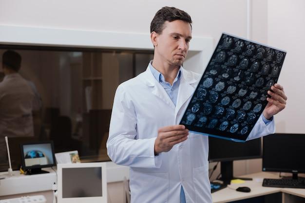 Typische werkdagen. ernstige knappe ervaren radioloog die een mri-scanfoto vasthoudt en deze onderzoekt terwijl hij in het laboratorium werkt