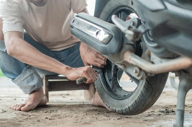 Tyre repairman gebruikt een bandenschraper om motorbanden te verwijderen in een bandenreparatiewerkplaats